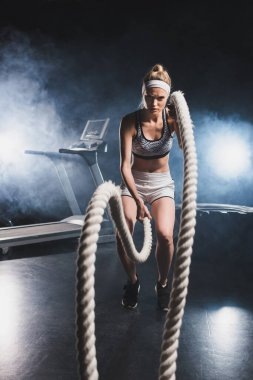 Selective focus of sportswoman exercising with battle rope in sports center with smoke stock vector