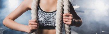Panoramic shot of sportswoman holding battle rope near smoke in gym stock vector