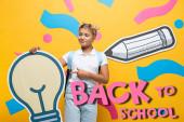 Zmatená školačka ukazující prstem na papírovou žárovku v blízkosti dekorativních prvků a zpět do školy písmo na žluté