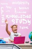 Školačka sedí se zvednutou rukou poblíž notebooku, telefonu, nápisu a papírového umění na růžové