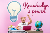 Excited schoolkid having idea near gadgets, paper artwork and knowledge is power lettering on pink background
