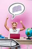 Excited kid pointing with fingers at speech bubble with book illustration near laptop, smartphone and globe on pink