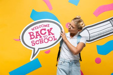 Skeptical schoolgirl holding speech bubble with welcome back to school lettering near paper pencil and abstract elements on yellow stock vector