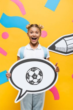 Excited schoolchild holding speech bubble with football illustration near paper elements and pencil on yellow stock vector