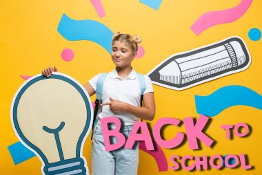 Confused schoolgirl pointing with finger at paper light bulb near decorative elements and back to school lettering on yellow stock vector