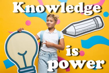 Confused schoolgirl pointing with finger at paper light bulb near decorative elements and knowledge is power lettering on yellow stock vector