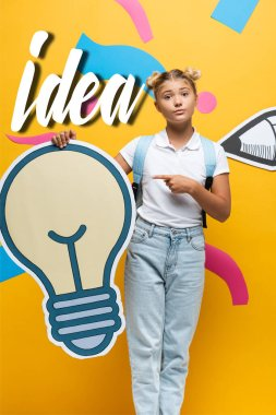 Schoolgirl with backpack pointing with finger at decorative light bulb near paper art and idea lettering on yellow background stock vector