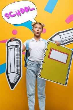 Pensive schoolgirl holding paper pencil and notebook near speech bubble illustration with school lettering on yellow stock vector