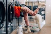 junge Frau checkt Waschmaschine in der Nähe von Waschmittelflasche und Einkaufswagen mit schmutziger Kleidung