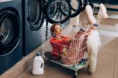 Stilvolle Frau sitzt im Einkaufswagen neben Waschmaschinen und Flasche mit Waschmittel im Waschsalon
