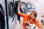 stílusos nő ül a kosárban, és a gazdaság ruházat közelében mosógép mosodában
