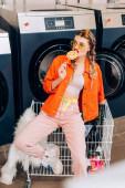 Stilvolle Frau mit Sonnenbrille beißt Lutscher neben Einkaufswagen mit Kleidung und Waschmaschinen im Waschsalon