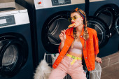 Trendfrau mit Sonnenbrille beißt Lutscher neben Einkaufswagen und Waschmaschinen im Waschsalon