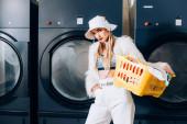 stylová žena ve falešné kožešinové bundě a klobouku drží koš s prádlem a stojí s rukou v kapse v blízkosti praček v prádelně