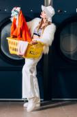 stylische junge Frau in Kunstpelzjacke und Hut mit Korb und Blick auf Wäsche in der Nähe von Waschmaschinen im Waschsalon