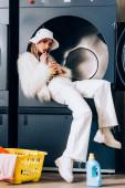 Fotografie stylische Frau in Kunstpelzjacke und Hut mit Plastikbecher und trinkbarem Orangensaft in der Nähe von Korb mit Wäsche und Waschmaschine