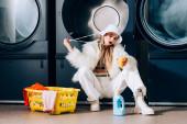 stylische Frau in Kunstpelzjacke und Hut mit Plastikbecher mit Orangensaft in der Nähe von Korb mit Wäsche und Waschmaschinen im Waschsalon