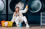 Fotografie Frau in Kunstpelzjacke hält Plastikbecher mit Orangensaft neben Korb mit Wäsche, Waschmittelflasche und Waschmaschinen im Waschsalon