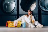 Fotografie stylische Frau in Kunstpelzjacke mit Plastikbecher mit Orangensaft in der Nähe von Korb mit Wäsche, Waschmittelflasche und Waschmaschinen im Waschsalon