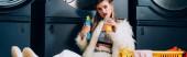 Frau in Kunstpelzjacke mit Plastikbecher mit Orangensaft neben Korb mit Wäsche im Waschsalon, Banner