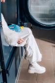 Ausgeschnittene Ansicht einer Frau, die eine Flasche mit Waschmittel in der öffentlichen Waschmaschine sitzt