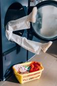 nohy ženy trčí z pračky v blízkosti koše se špinavým prádlem