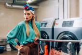 Stilvolle Frau im Turban, die mit der Hand in der Tasche neben Waschmaschinen im Waschsalon steht