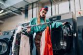 junge und stylische Frau im Turban steht neben Kleiderständern und Waschmaschinen im modernen Waschsalon