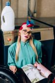 trendi nő szemüveges és turbán holding magazin közelében mosógép nyilvános mosodában