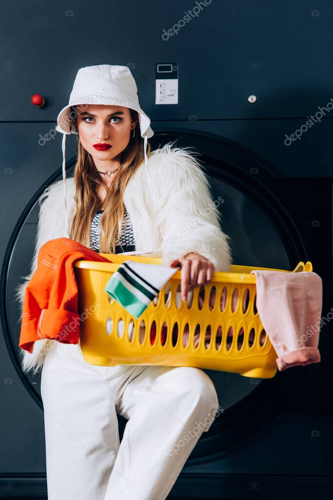 Stylish young woman in faux fur jacket and hat holding basket with laundry near washing machine in laundromat stock vector