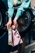 kivágott kilátás fiatal nő holding magazin nyilvános mosodában