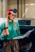 trendi nő szemüveges és turbán tartó papír csésze és újságot olvasni a mosodában