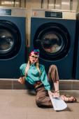 junge Frau mit Brille und Turban hält Pappbecher und Zeitung in der Hand, während sie im Waschsalon auf dem Boden sitzt