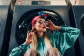 Stylische junge Frau mit Brille und Turban schaut in der Nähe der Waschmaschine weg