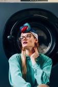 stylische junge Frau mit Brille und Turban im Waschsalon