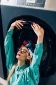 stylová mladá žena v brýlích a turban dotýkání dveří pračky v prádelně