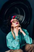 stílusos fiatal nő szemüveges és turbán ül csukott szemmel közel mosógép