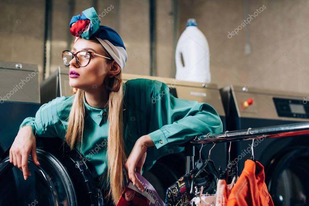Trendy woman in glasses and turban holding magazine near modern washing machine stock vector