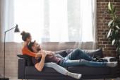 mladý pár relaxovat na pohovce v blízkosti okna doma