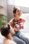 izgatott nő csukott szemmel tartó ajándék doboz közel férfi elmosódott előtérben