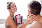 glückliche sinnliche Frau hält Geschenkschachtel und berührt Mann auf verschwommenem Vordergrund