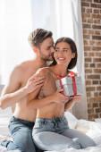 Hemdloser Mann umarmt glückliche Freundin mit Geschenkbox im Schlafzimmer