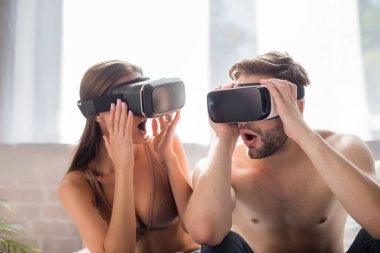 Shocking couple using and touching vr headsets in bedroom stock vector