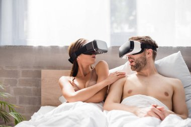 Excited couple looking at each other while lying in bed and using vr headsets stock vector
