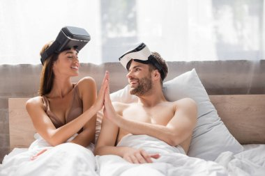 Young lovers with vr headsets looking at each other and giving high five stock vector
