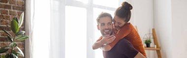 Joyful woman piggybacking on happy boyfriend at home, banner stock vector