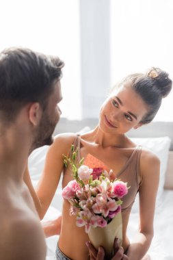 Happy, sexy woman holding flowers and looking at man on blurred foreground stock vector