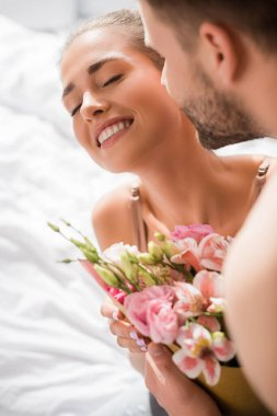 Man embracing happy girlfriend holding flowers with closed eyes stock vector