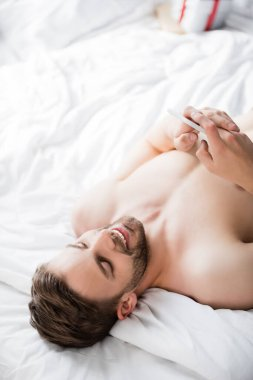 Overhead view of shirtless man lying in bed and chatting on mobile phone stock vector