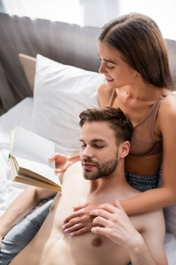 Seductive woman touching shirtless boyfriend while reading book in bedroom stock vector